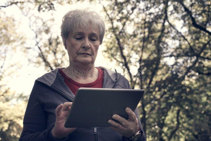 Mulher superior que está na floresta e que datilografa em iPod clo imagens de stock