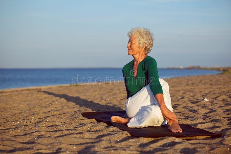 Mulher superior que executa uma rotina da ioga na praia imagem de stock
