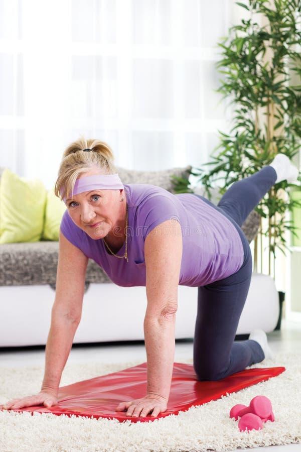 Mulher superior que exercita em casa fotos de stock