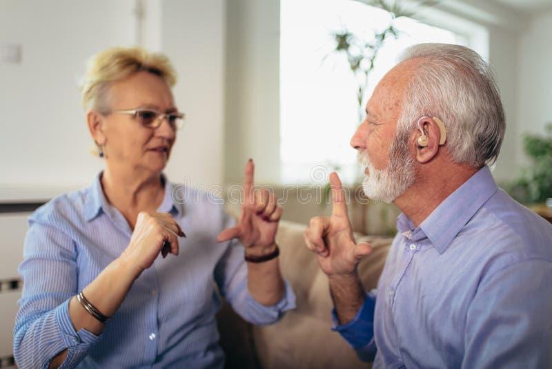 Mulher superior que fala usando a linguagem gestual com seu homem do preju?zo de audi??o foto de stock royalty free
