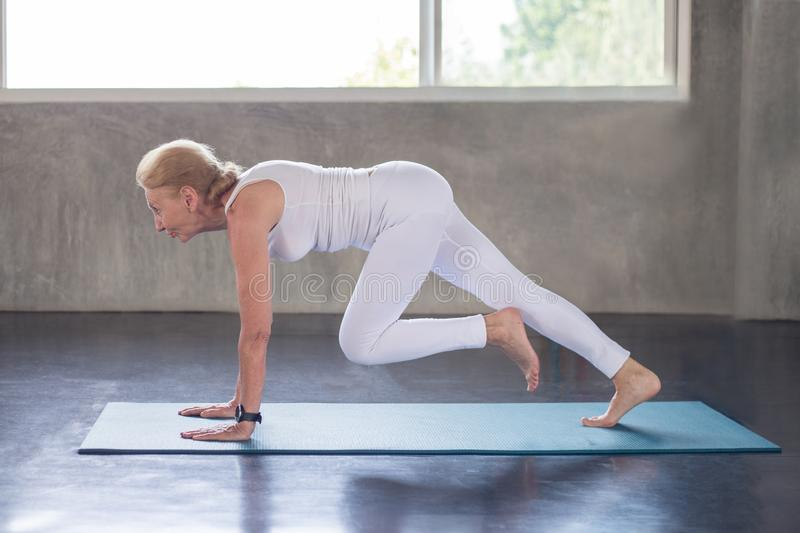 Mulher superior que faz a ioga no gym da aptidão exerc?cio envelhecido da senhora Exerc?cio f?mea velho Treinamento maduro do esp fotografia de stock royalty free