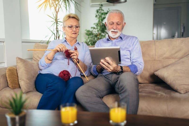 A mulher superior que faz malha a roupa de l? e o seu marido est? usando a tabuleta digital imagens de stock royalty free