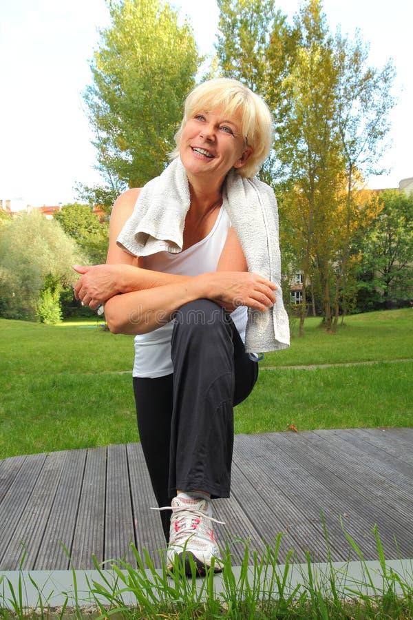 Mulher superior que faz o esporte com a toalha sobre o pescoço imagens de stock