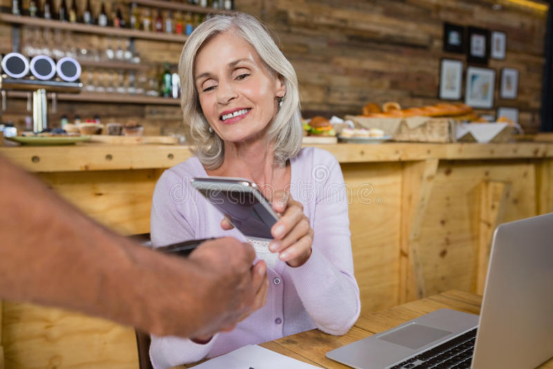 Mulher superior que faz o pagamento com a tecnologia de NFC no telefone celular foto de stock