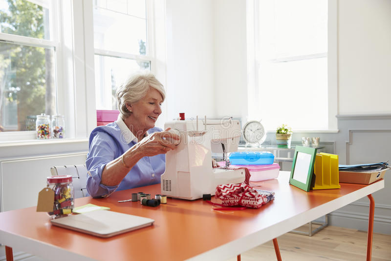 Mulher superior que faz a roupa usando a máquina de costura em casa fotos de stock royalty free