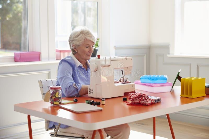 Mulher superior que faz a roupa usando a máquina de costura em casa imagens de stock royalty free