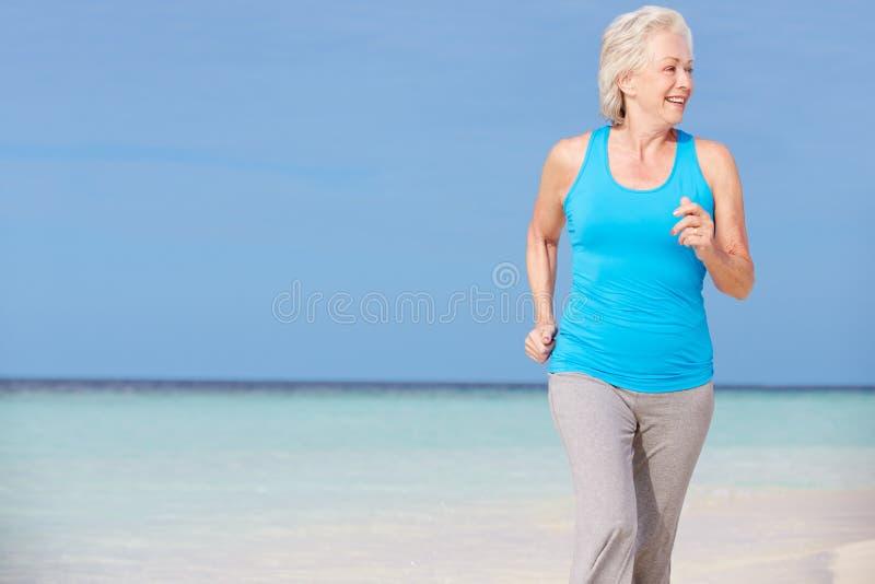 Mulher superior que funciona na praia bonita imagem de stock royalty free