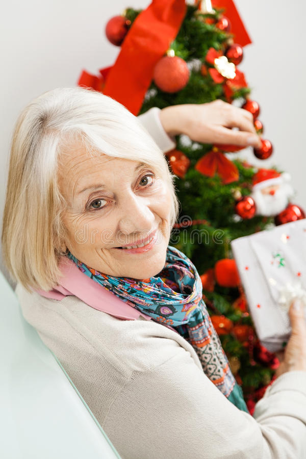 Mulher superior que guarda atual pela árvore de Natal fotografia de stock royalty free