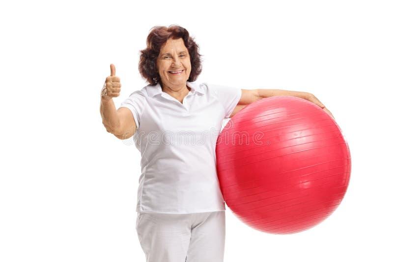 Mulher superior que guarda a bola dos pilates e que dá o polegar acima fotografia de stock