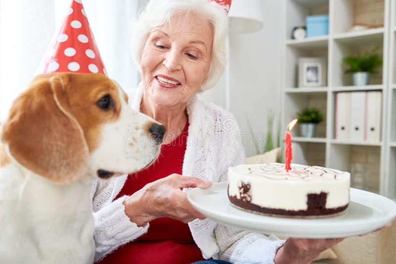 Mulher superior que guarda o bolo de aniversário fotos de stock
