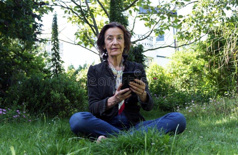 Mulher superior que lê um eBook no jardim fotografia de stock