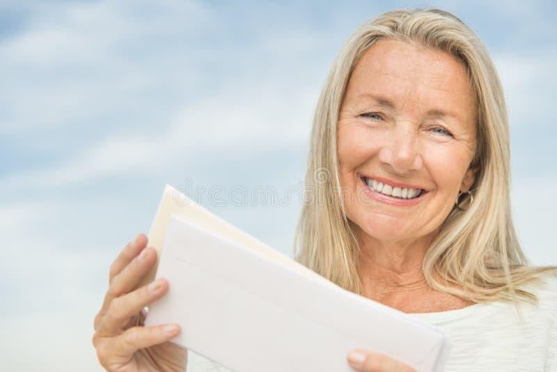 Mulher superior que mantem envelopes contra o céu foto de stock