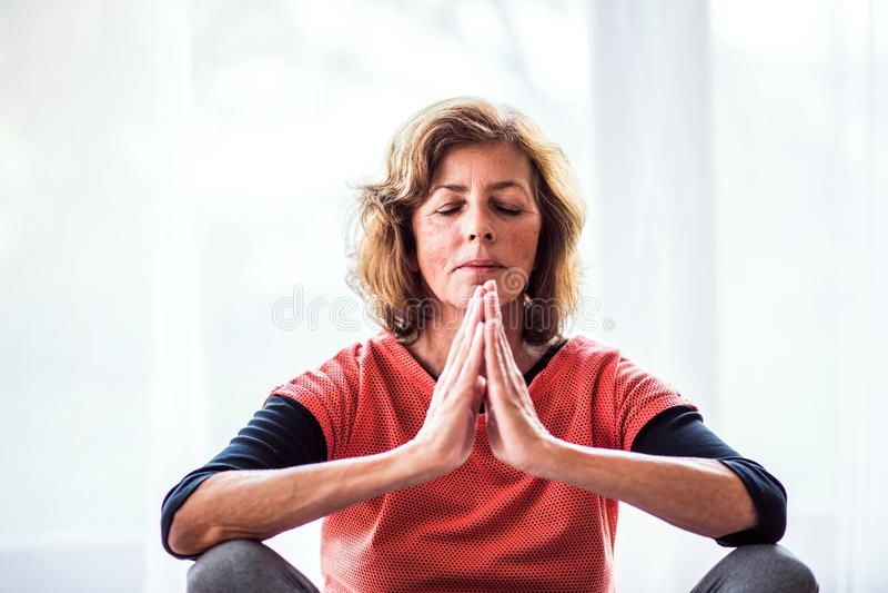 Mulher superior que medita em casa foto de stock