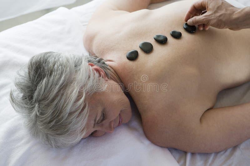 Mulher superior que obtem a terapia de pedra quente imagem de stock