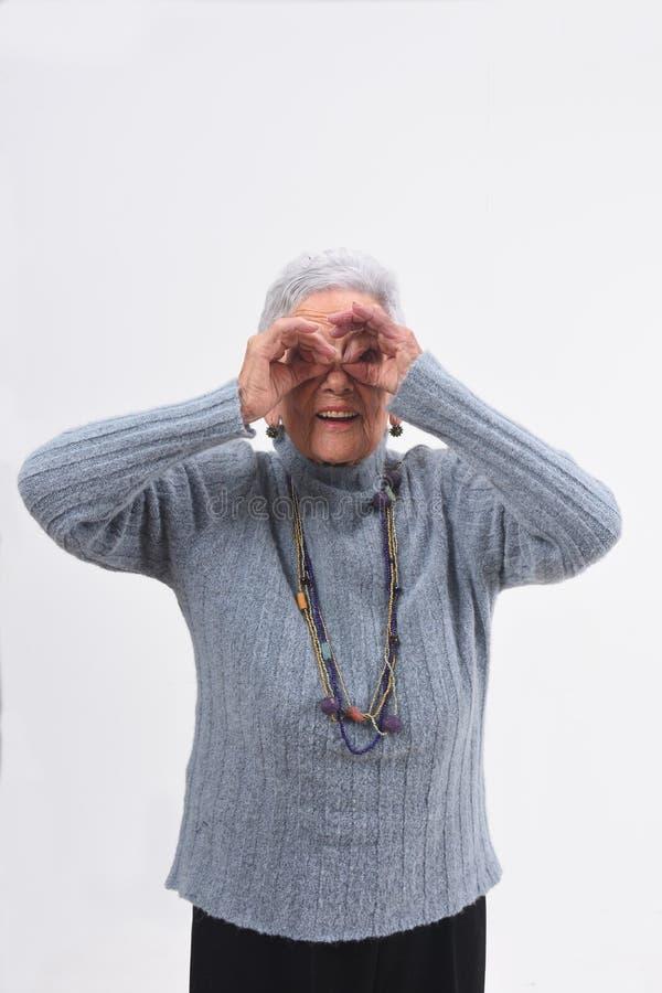 Mulher superior que olha através dos dedos como se vestindo vidros no fundo branco fotografia de stock royalty free