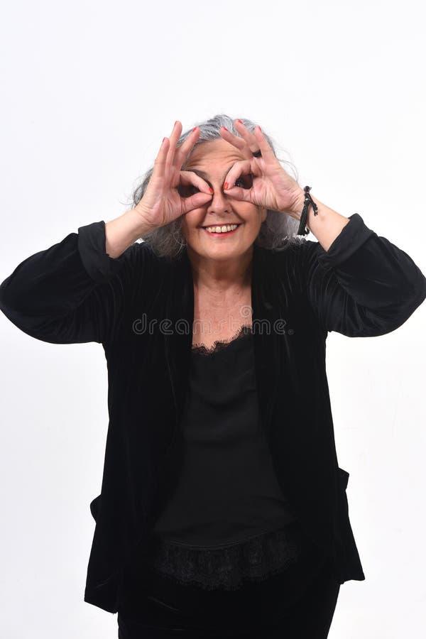 Mulher superior que olha através dos dedos como se vestindo vidros no fundo branco fotos de stock royalty free