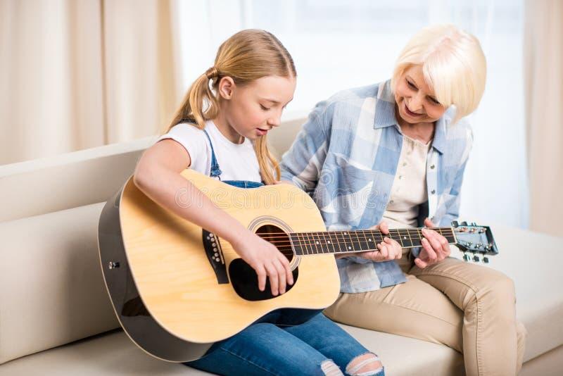 Mulher superior que olha a menina do preteen que joga a guitarra acústica no sofá fotografia de stock
