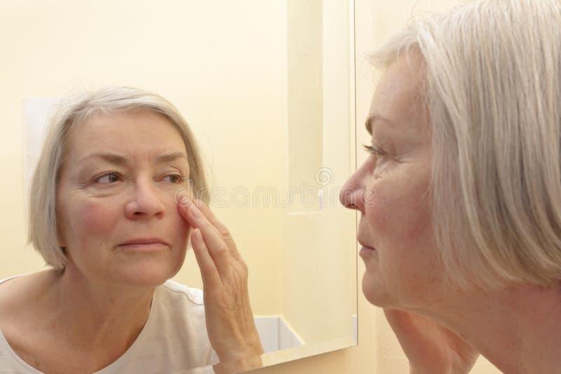 Mulher superior que olha o espelho dos enrugamentos foto de stock