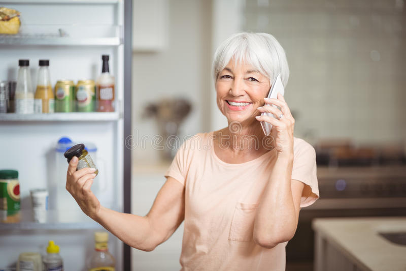 Mulher superior que olha o frasco ao falar no telefone celular na cozinha foto de stock royalty free