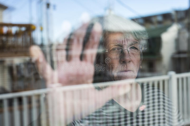 A mulher superior que olha para fora através de uma janela como comprime fotografia de stock