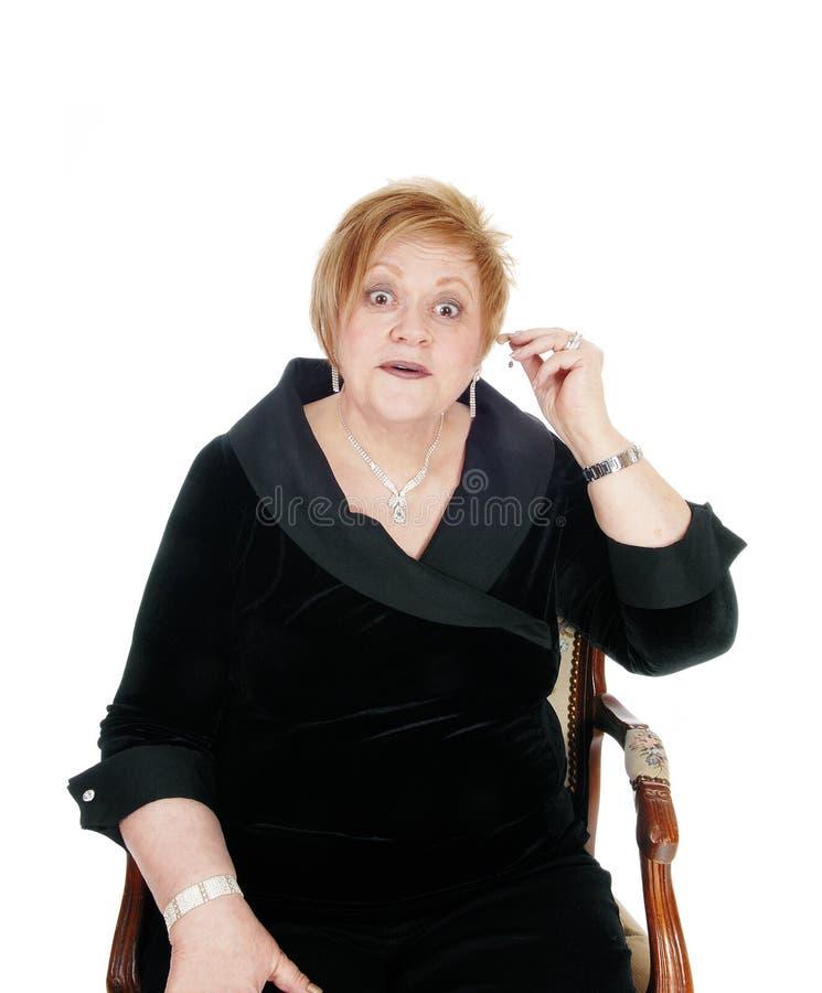 Mulher superior que põe a prótese auditiva sobre imagem de stock