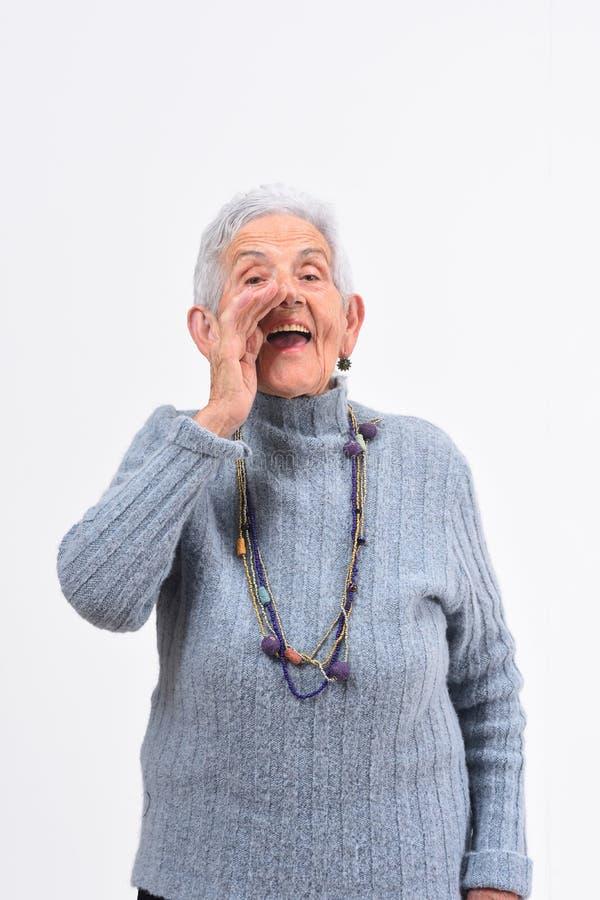 A mulher superior que põe uma mão no labo e está gritando no fundo branco fotos de stock royalty free