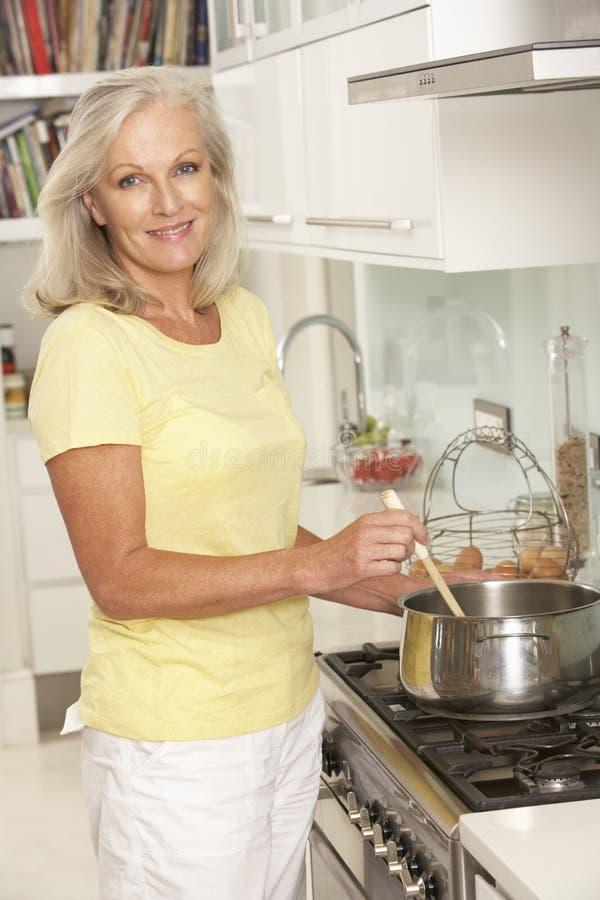 Mulher superior que prepara a refeição no fogão imagens de stock