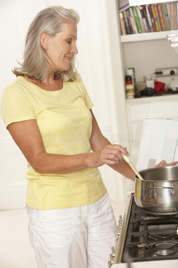 Mulher superior que prepara a refeição no fogão imagens de stock royalty free