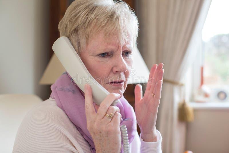 Mulher superior que recebe chamada telefônica indesejável em casa imagem de stock