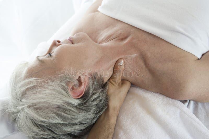 Mulher superior que recebe a massagem do pescoço em termas fotografia de stock royalty free