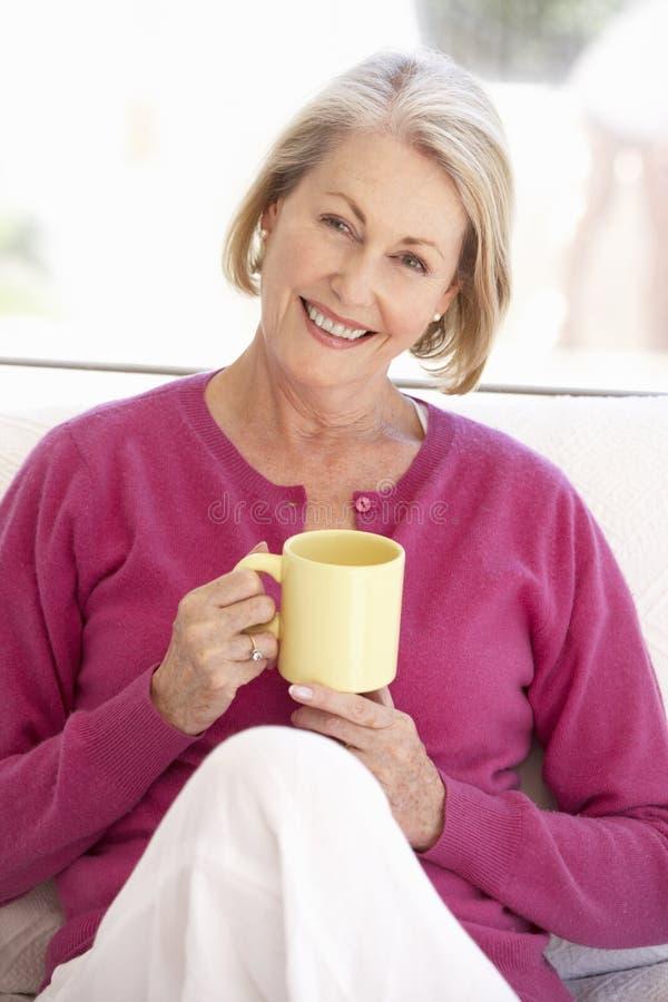 Mulher superior que relaxa em casa com bebida quente fotografia de stock