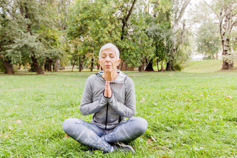 Mulher superior que relaxa na pose da ioga exterior imagem de stock