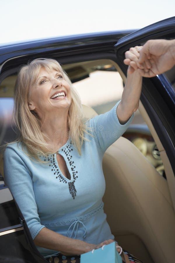 Mulher superior que sai de um carro foto de stock royalty free