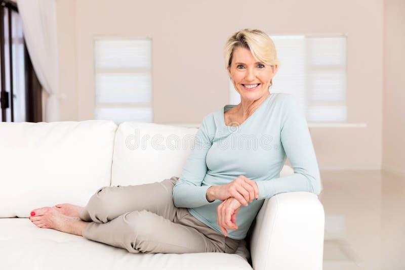 Mulher superior que senta-se em casa imagens de stock