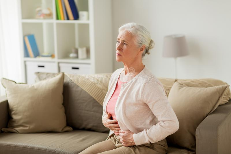 Mulher superior que sofre da dor de estômago em casa imagem de stock royalty free