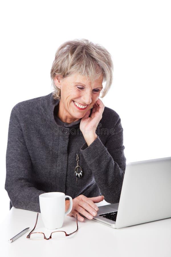 Mulher superior que surfa o Internet fotografia de stock royalty free
