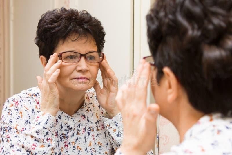 Mulher superior que tenta em monóculos novos e que olha si mesma no espelho imagens de stock royalty free