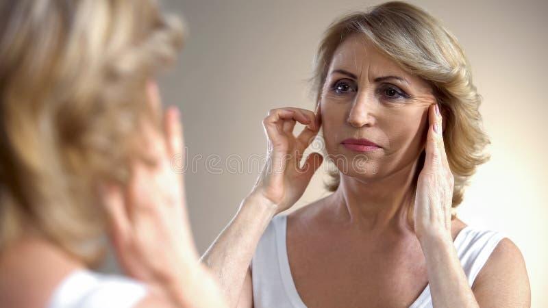 Mulher superior que toca na cara enrugada, pensando sobre injeções do botox, idade fotos de stock