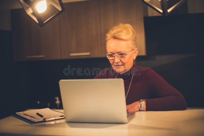 Mulher superior que trabalha em casa imagem de stock