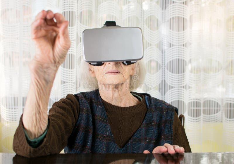 Mulher superior que usa óculos de proteção da realidade virtual foto de stock