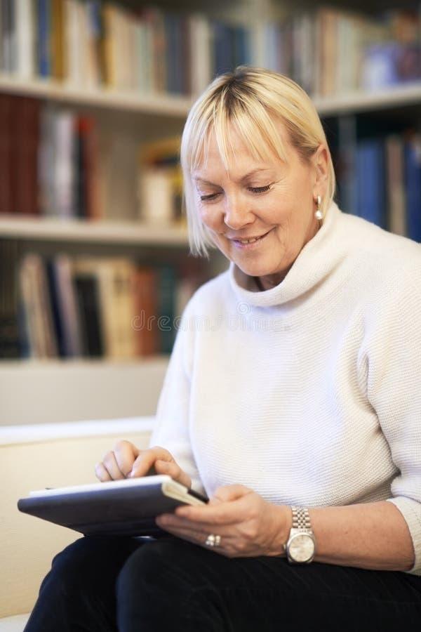 Mulher superior que usa o dispositivo de almofada do toque imagens de stock royalty free