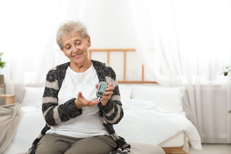 Mulher superior que usa o glucometer digital Controle do diabetes foto de stock royalty free