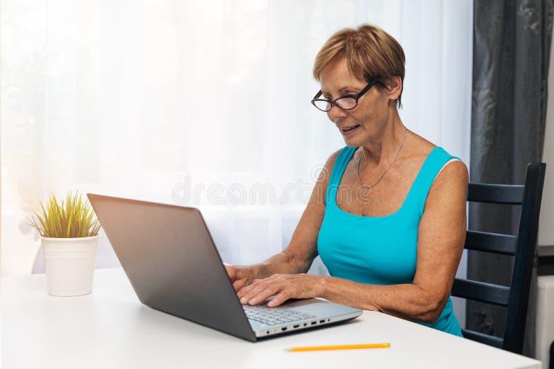 Mulher superior que usa o laptop em casa fotografia de stock royalty free