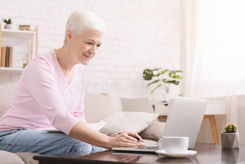 Mulher superior que usa o portátil em casa, educação em linha imagens de stock royalty free
