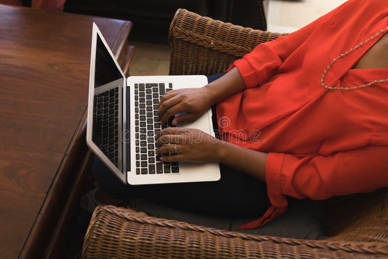 Mulher superior que usa o portátil na sala de visitas em casa fotos de stock royalty free