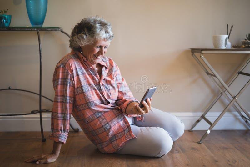 Mulher superior que usa o telefone celular ao sentar-se no assoalho fotografia de stock