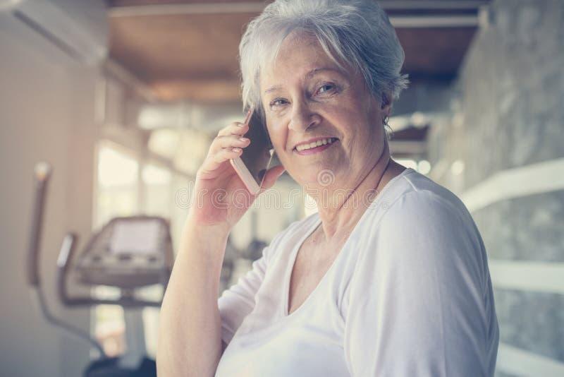 Mulher superior que usa o telefone esperto no gym Mulher que fala no foto de stock royalty free
