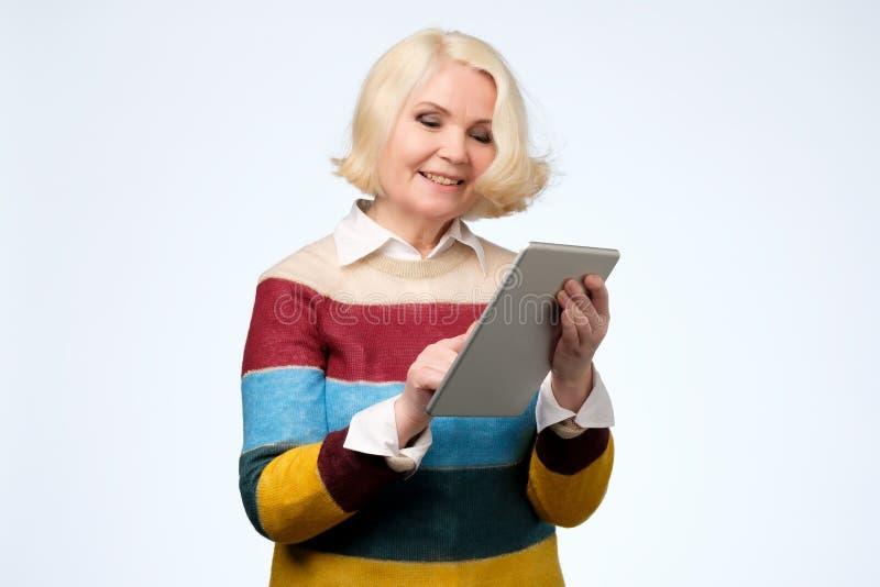 Mulher superior que usa os meios surfando da Web da tabuleta digital que conversam em linha, sorrindo imagem de stock royalty free