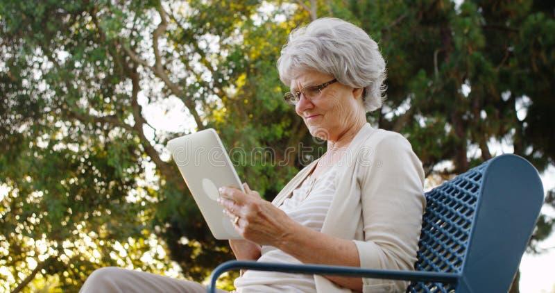 Mulher superior que usa a tabuleta no parque imagem de stock