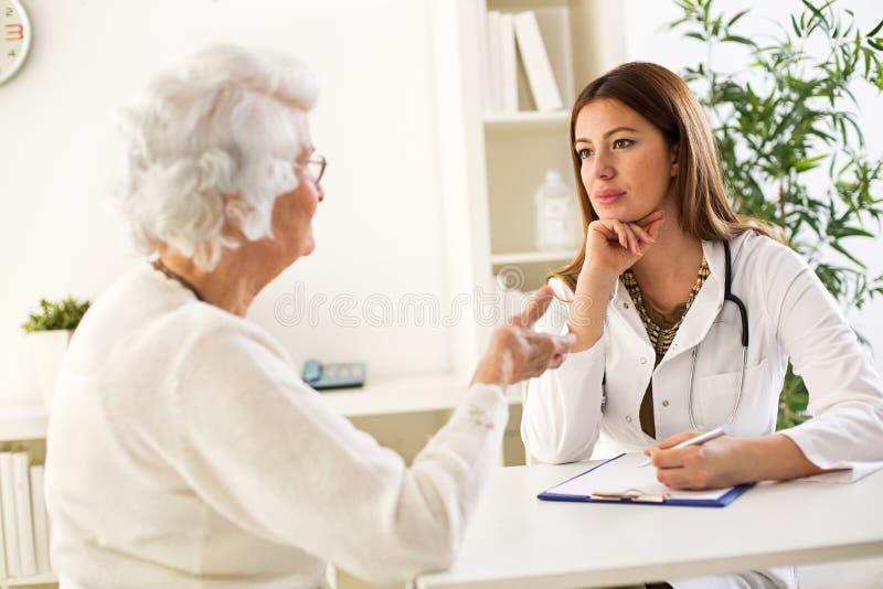 Mulher superior que visita um doutor foto de stock